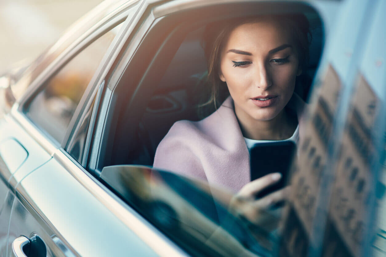A female passenger looking at her phone in the back seat of car