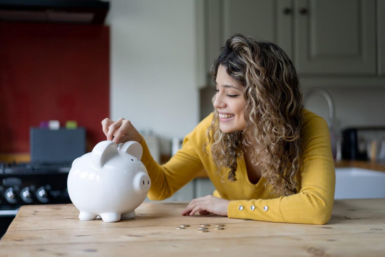 A happy woman putting money into a piggy bank