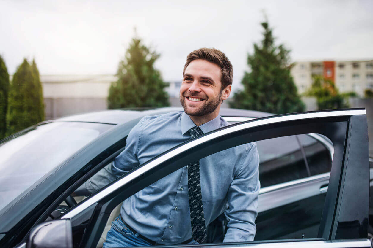 A business man getting out of a car