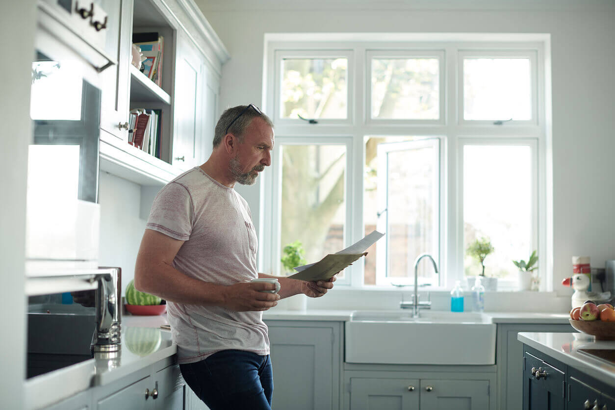 A man standing in his kitchen and reading a letter