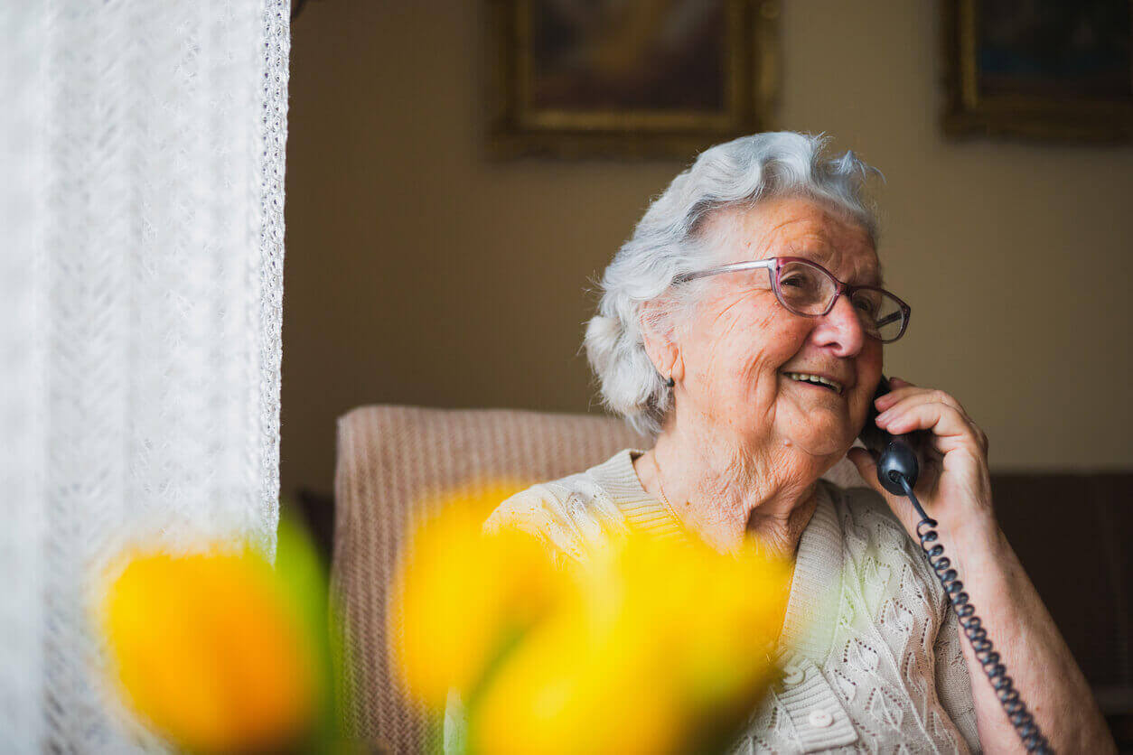 An elderly lady smiling while on the phone
