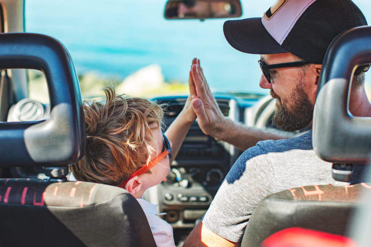 A man and son high-fiving in their car