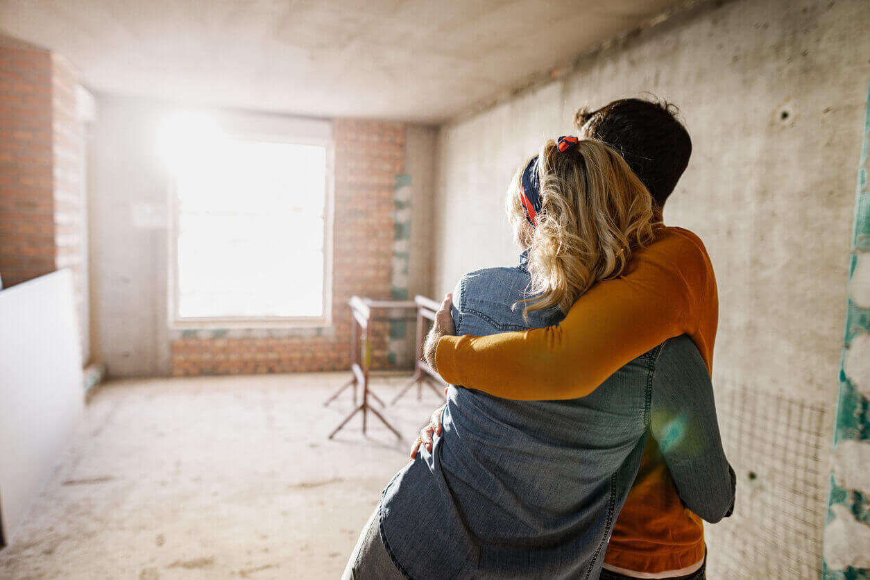 A young couple looking inside their home