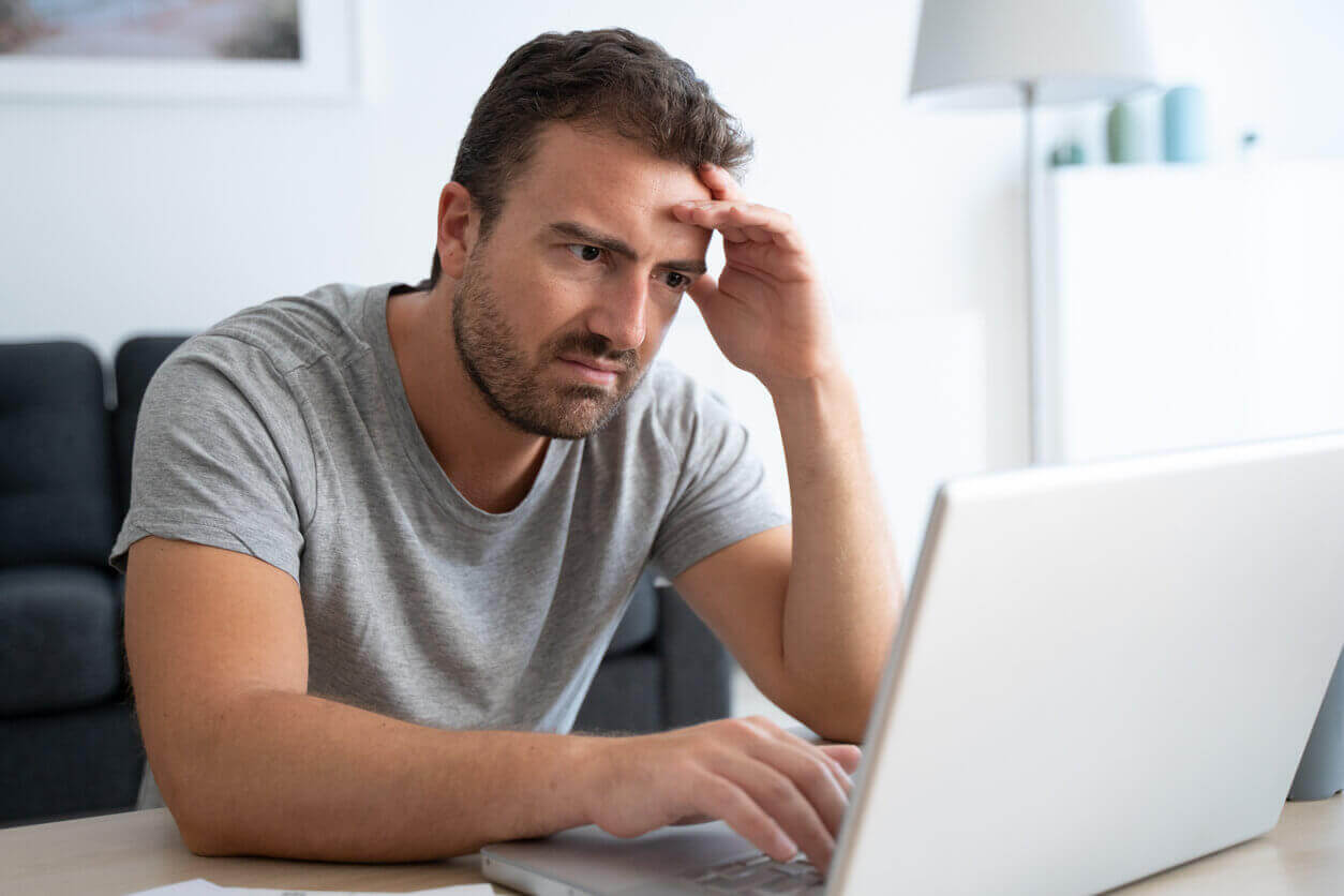 A confused man on his laptop unsure what answers to give