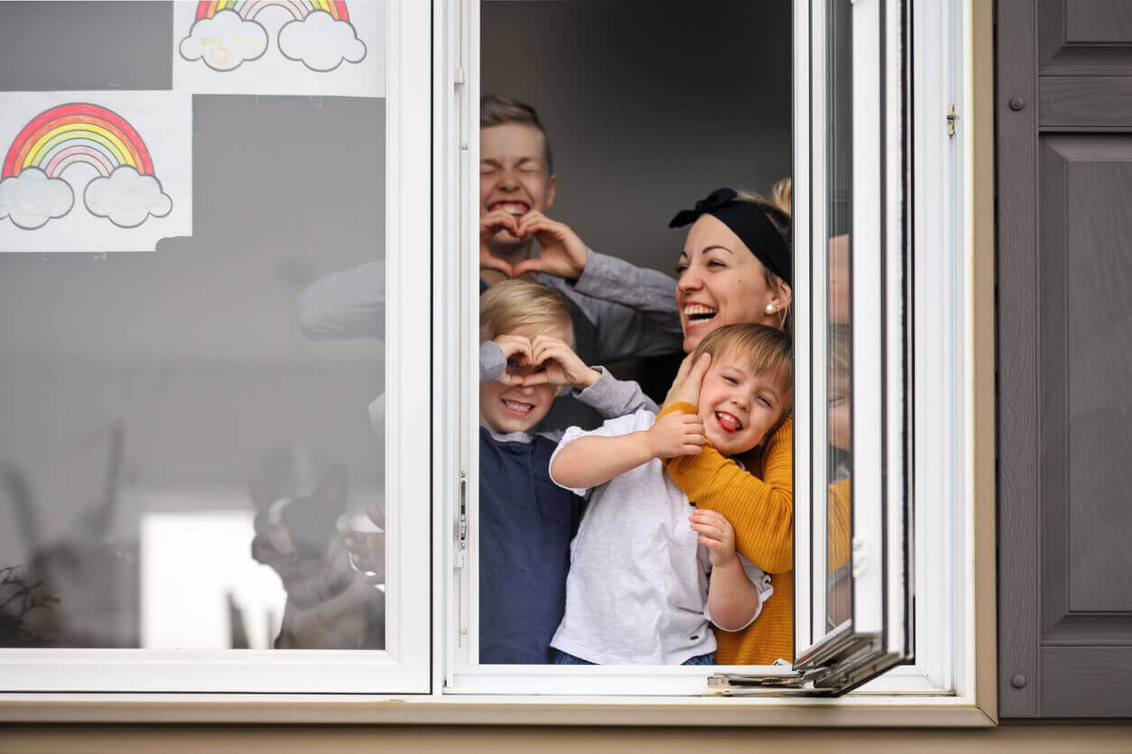 A happy family looking out the window during lockdown