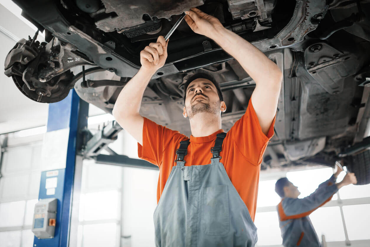 A mechanic working on the underneath of car