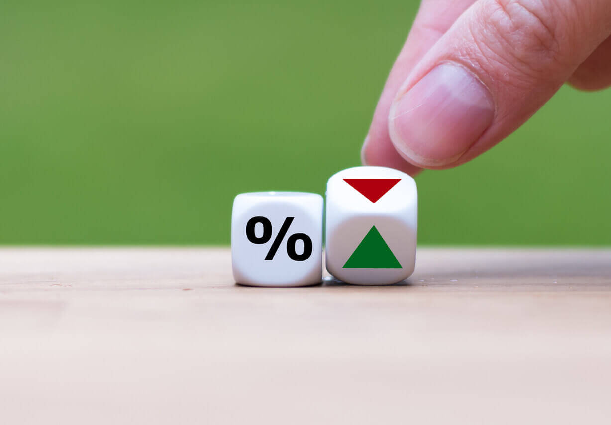 A dice with the percentage symbol and another showing a red arrow going down
