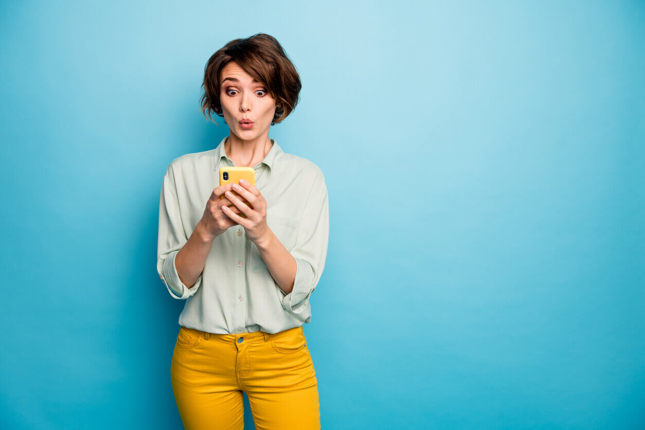 A surprised woman looking at her mobile phone