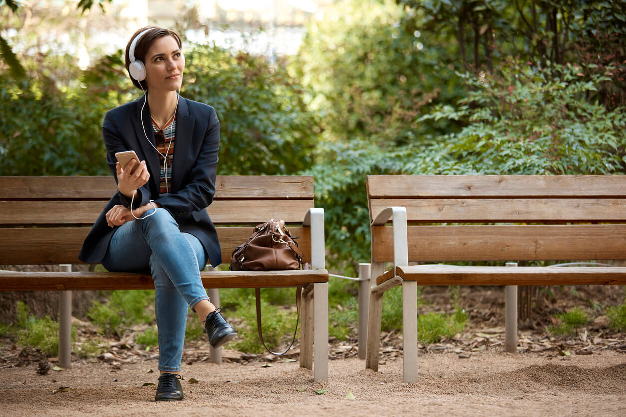 A lady sat on a bench with her handbag, mobile phone and earphones