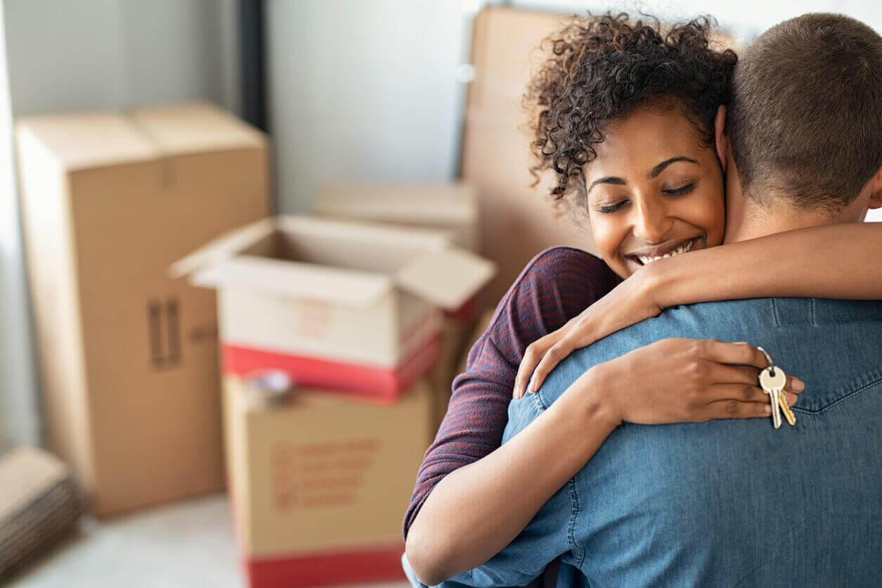 A couple hugging inside their new home