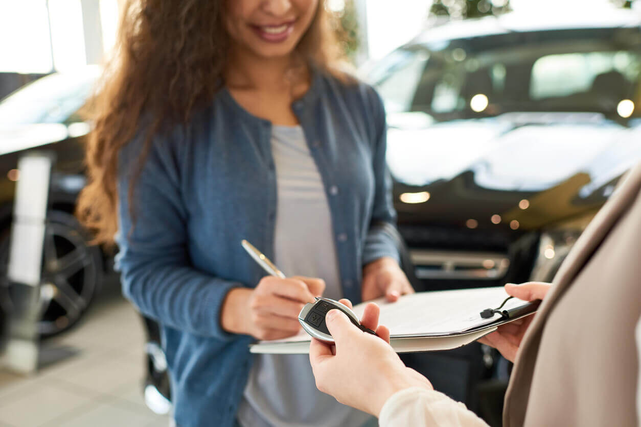 A young woman renting a car
