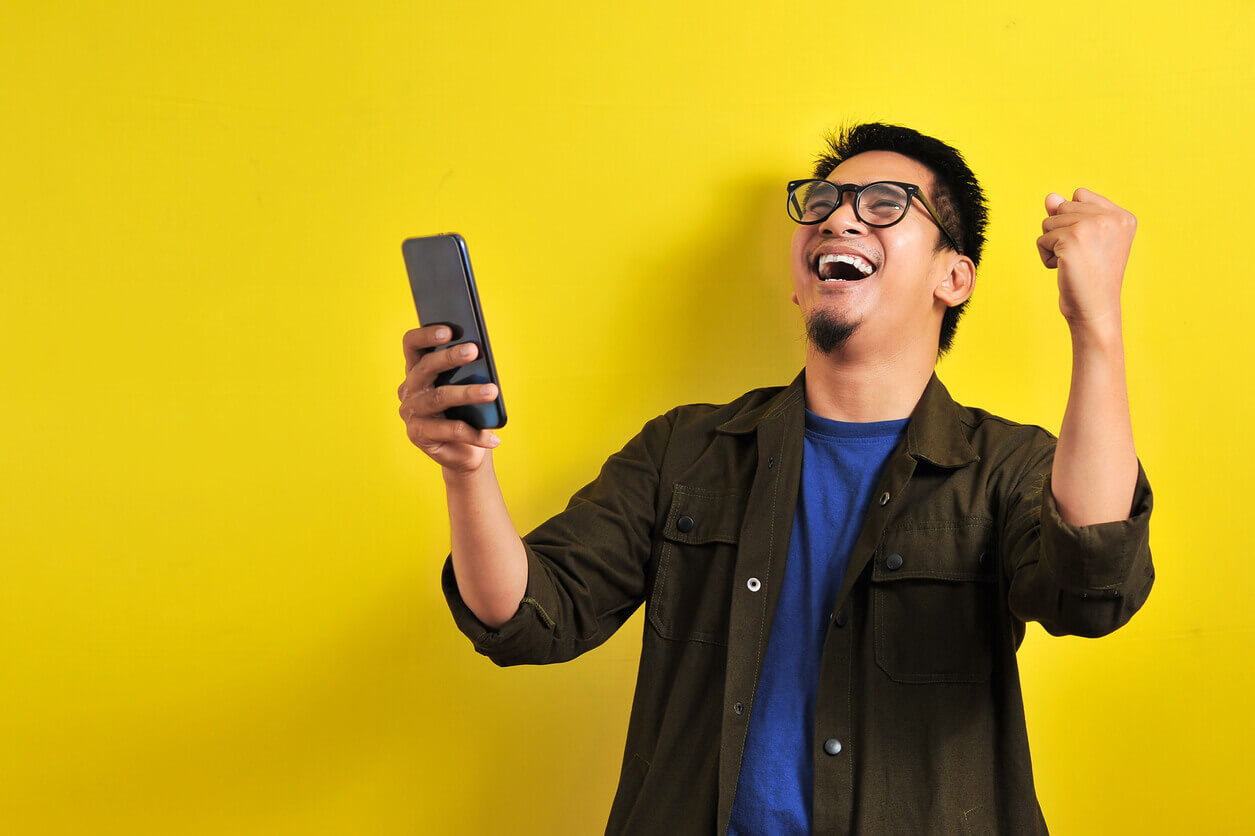A happy man on his phone with winning gesture