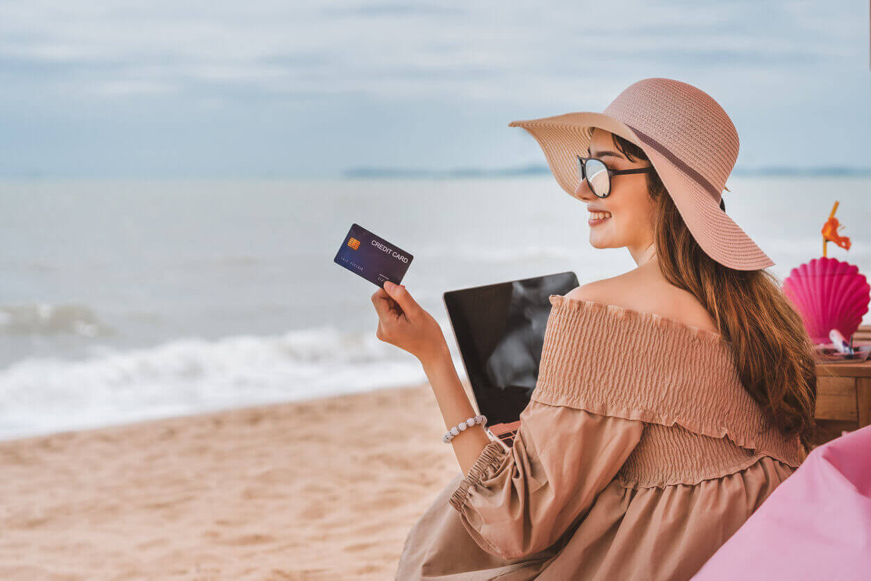 A woman on holiday using a travel credit card