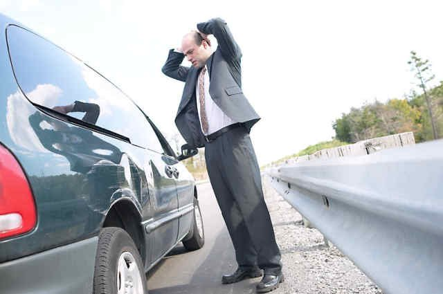 Driver looking at car hit by uninsured driver
