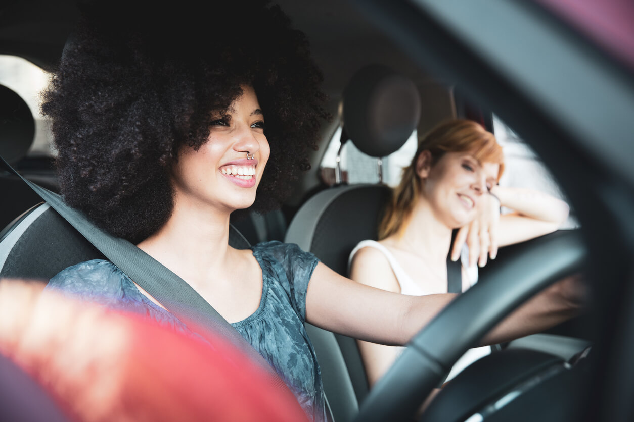A young woman driving a car with her friend in the passenger seat