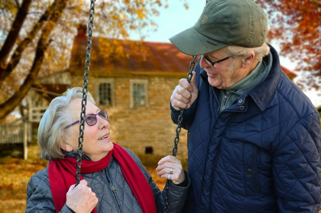 Over 70s couple sat on swing after organising life insurance