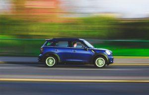 blue car driving down road