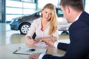woman signing contract for car finance