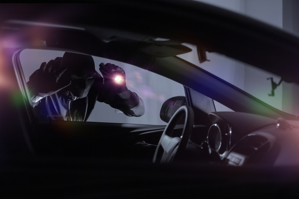 car thief looking in car with flashlight