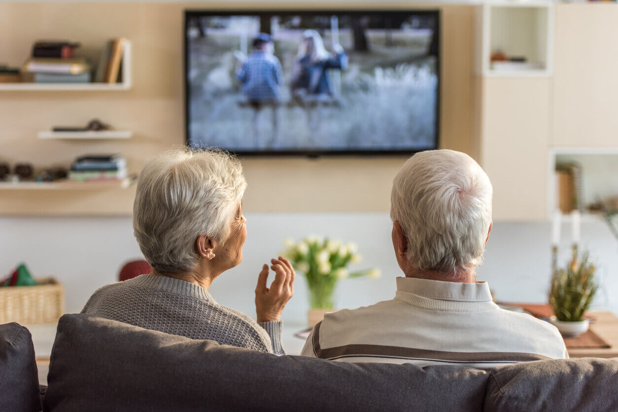An older couple watching tv in their home