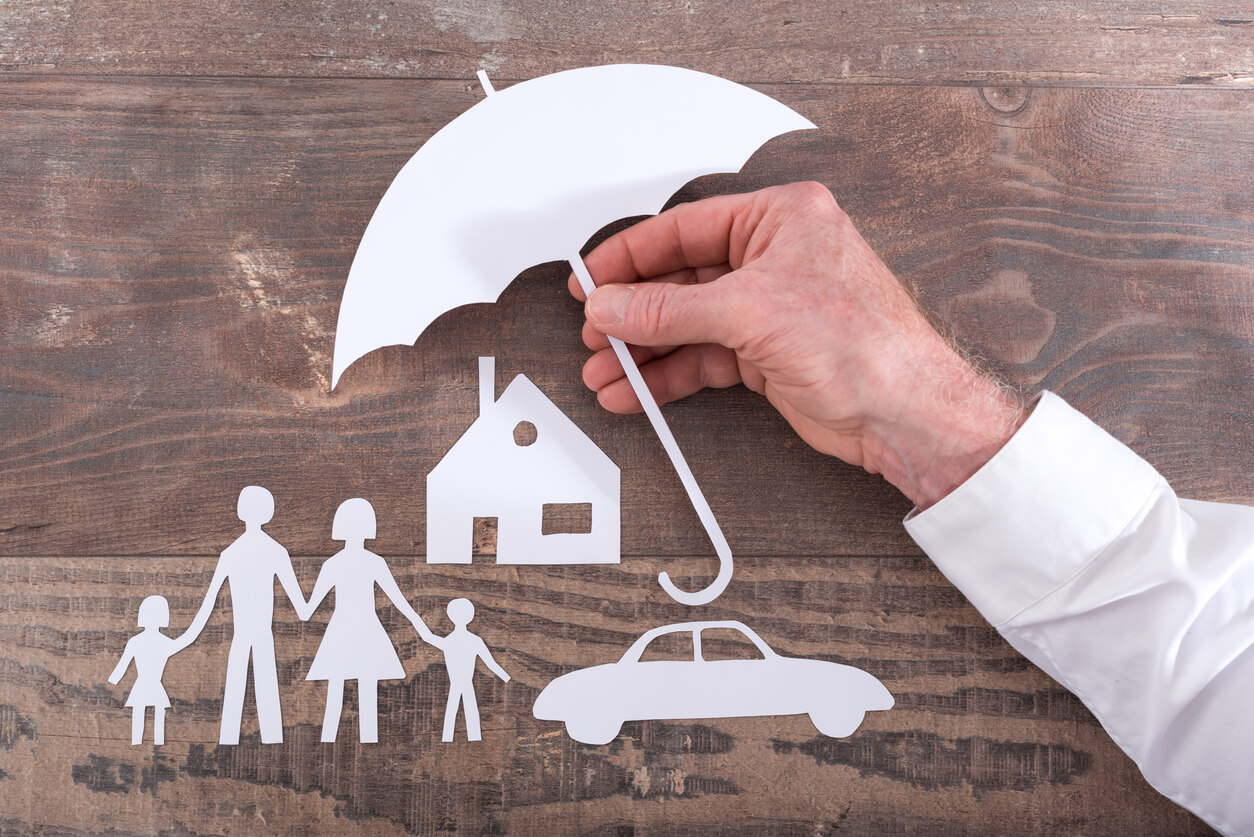 A paper umbrella covering cutouts of a family, house and car.