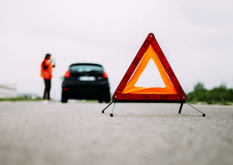 A person standing by their broken down car with red warning triangle in main focus.