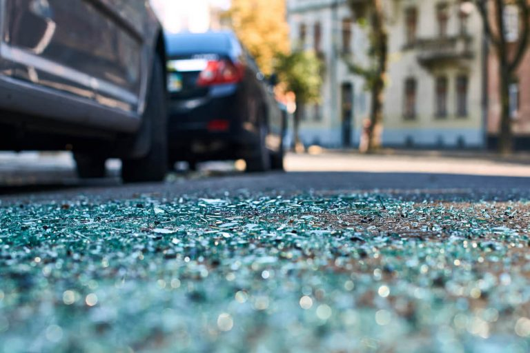 Shattered glass on the road at the scene of an accident.