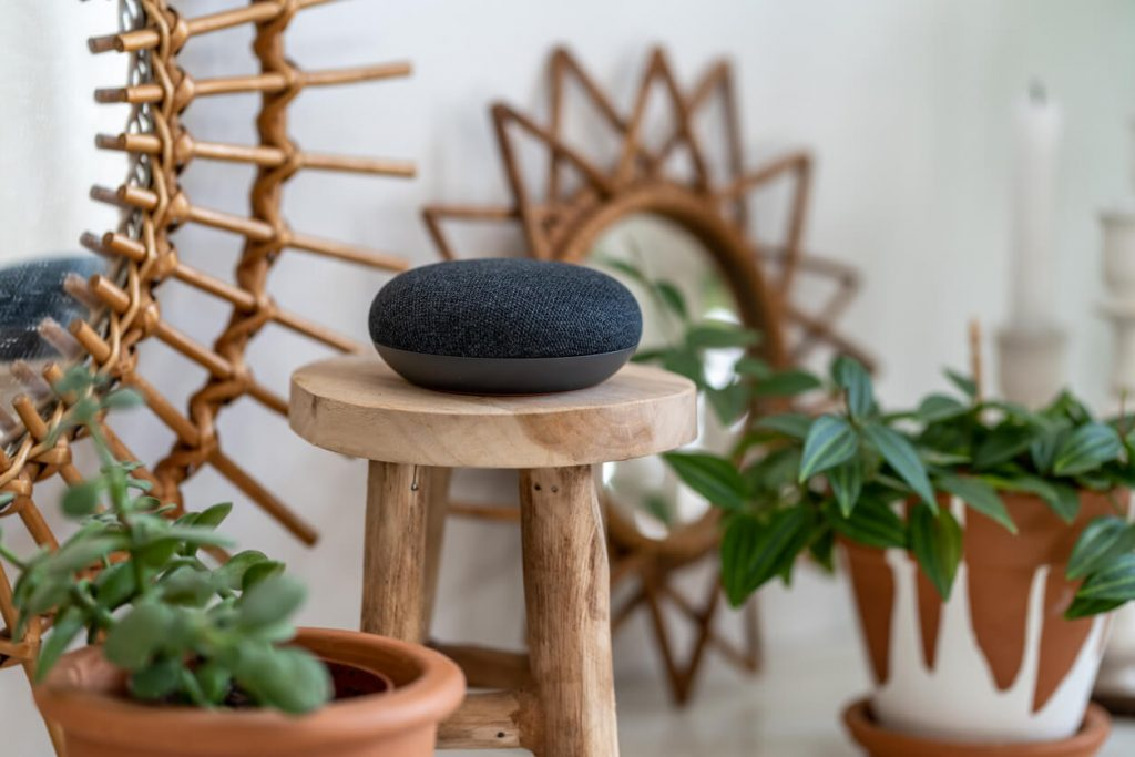 Google Home device on stool in living area.