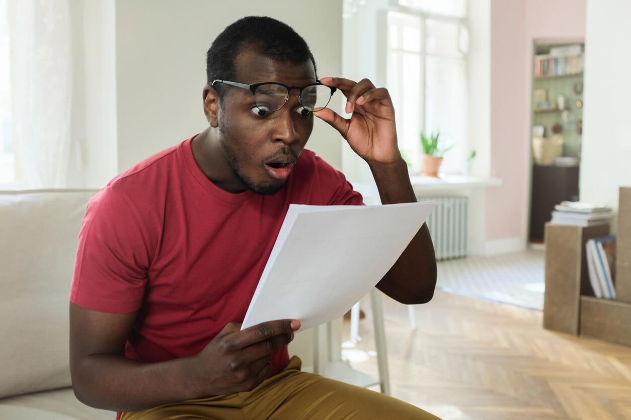 A man looking shocked at his car insurance bill