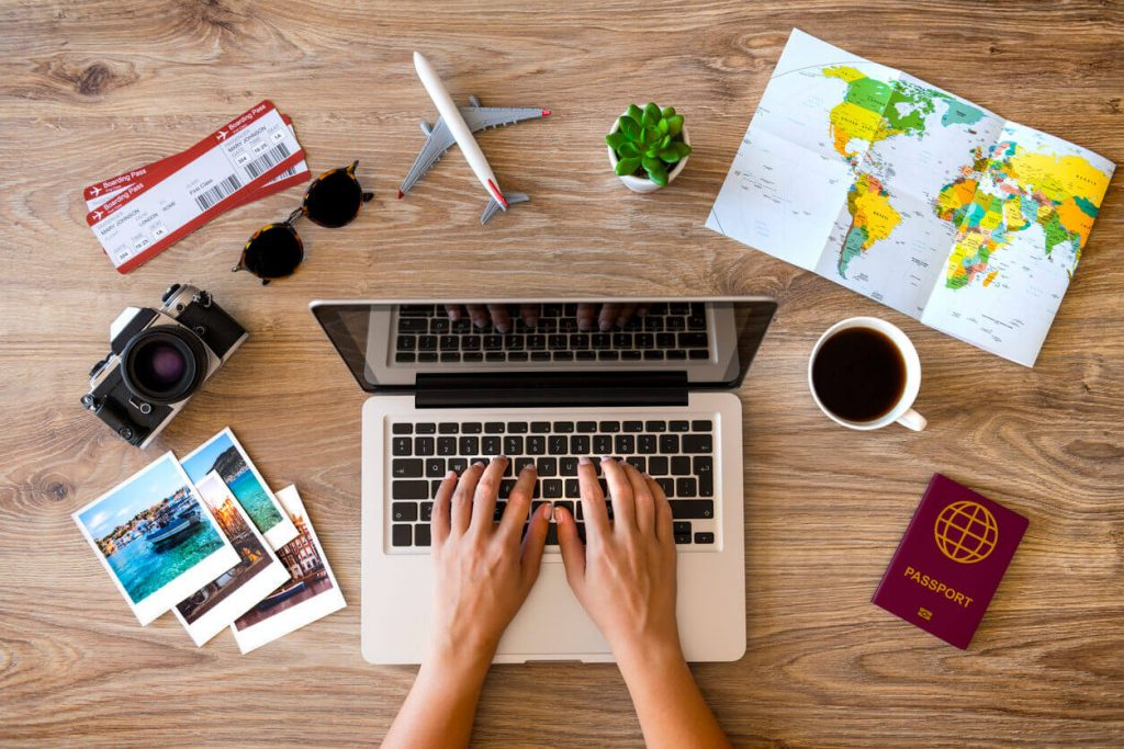 Person on laptop with cup of coffee and world map next to it.