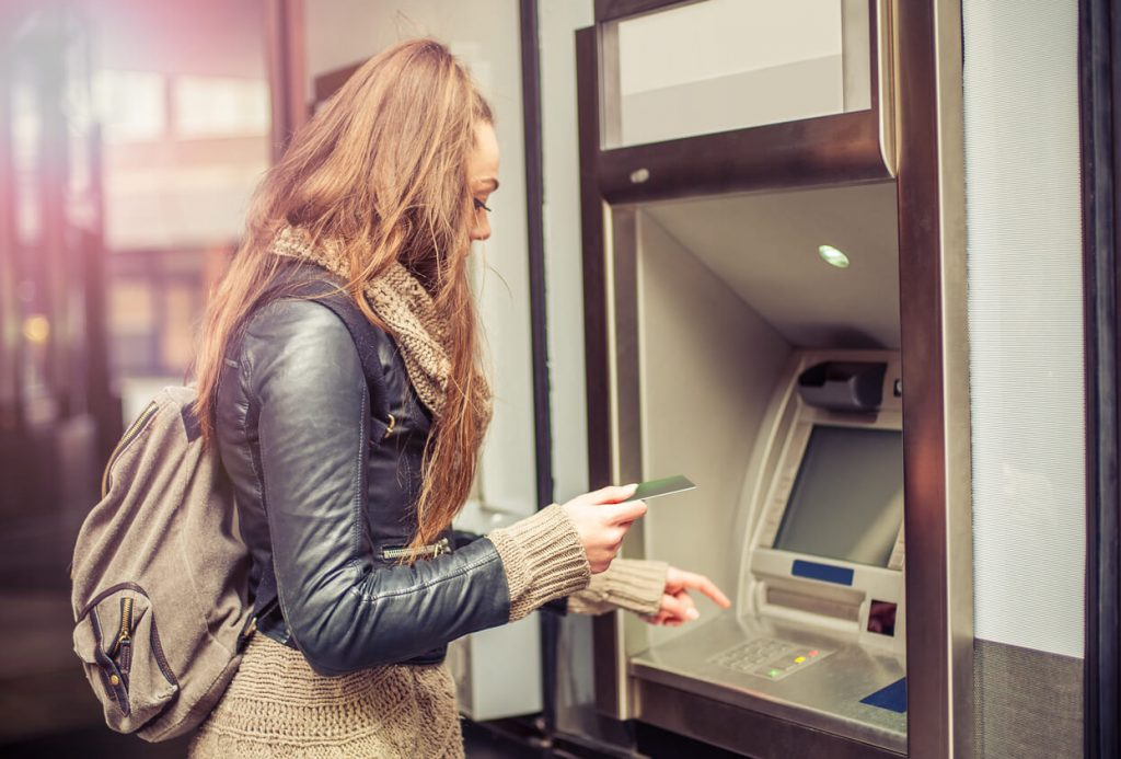 A student getting money out of an ATM machine