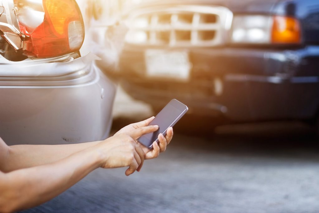 Man on mobile phone next to car accident