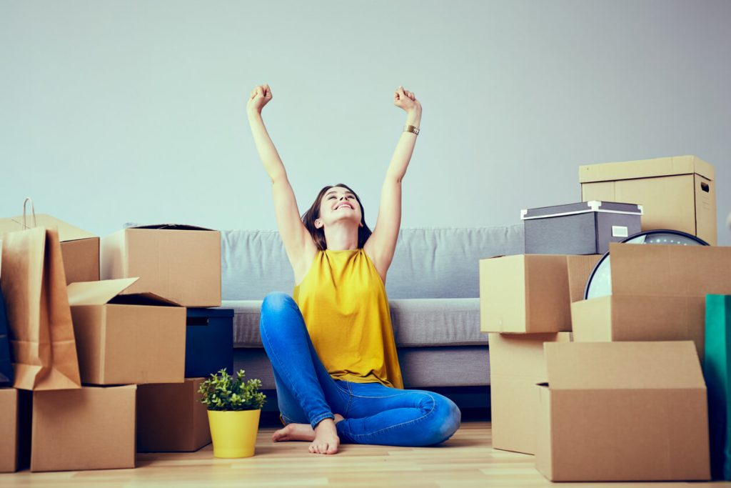 A young woman sat down in her new home with boxes surrounding her.