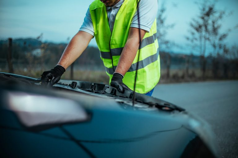 A man in high-vis vest looking at the car bonnet