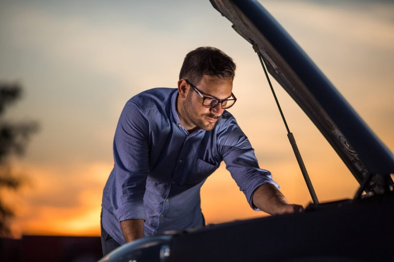 Business man inspecting his broken down car.