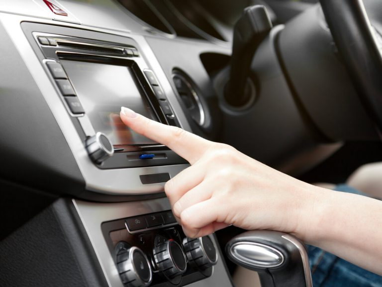 A woman touching the infotainment screen in her car