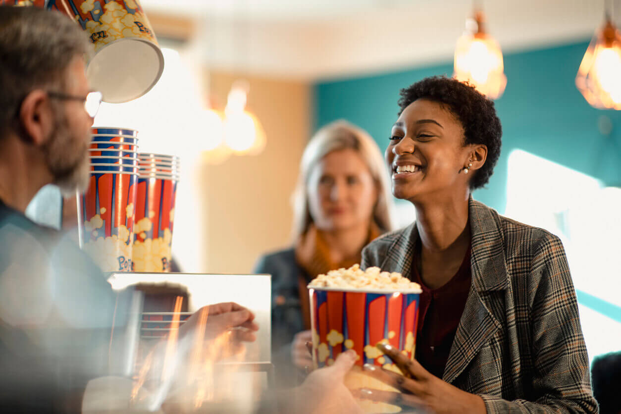 A woman smiling while getting popcorn