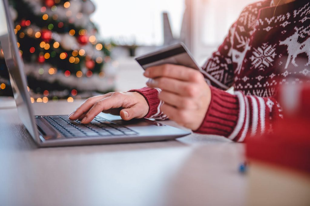 A woman shopping online with Christmas tree in the background