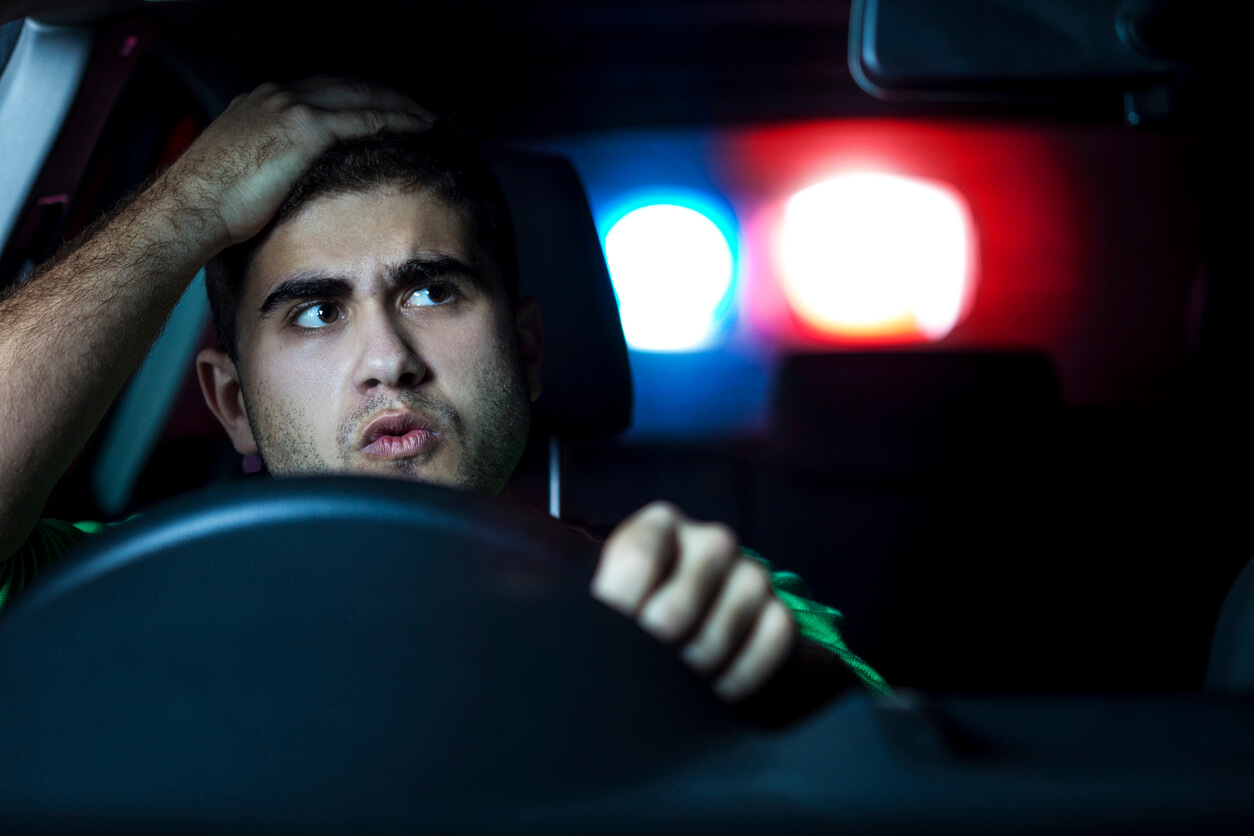 Man driving with police lights in rear-view mirror