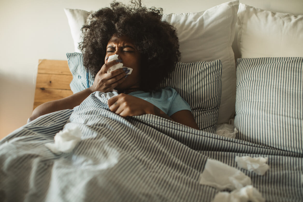 Woman ill in bed with tissues around her