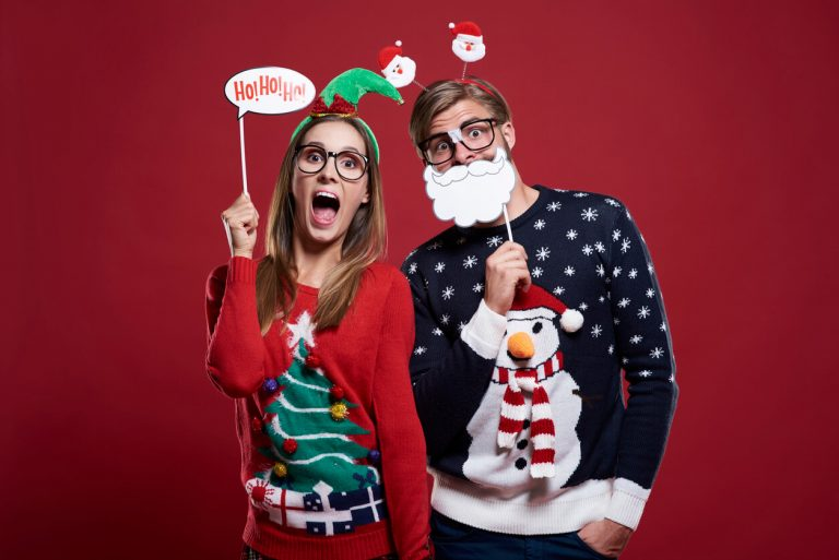A man and woman wearing Christmas jumpers