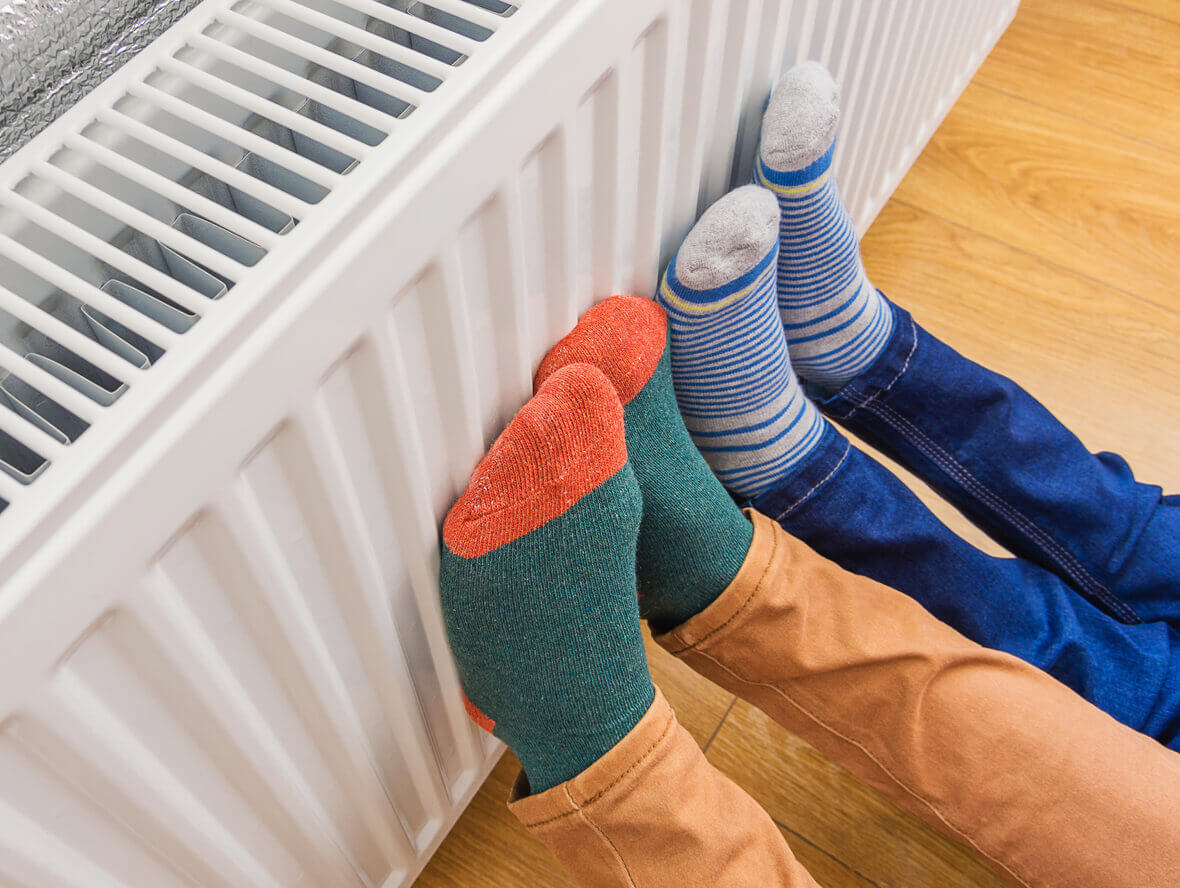 Two people's feet pressed against a radiator