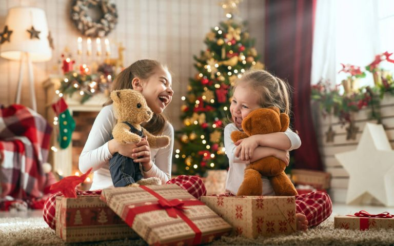 Two young girls opening presents on Christmas morning.