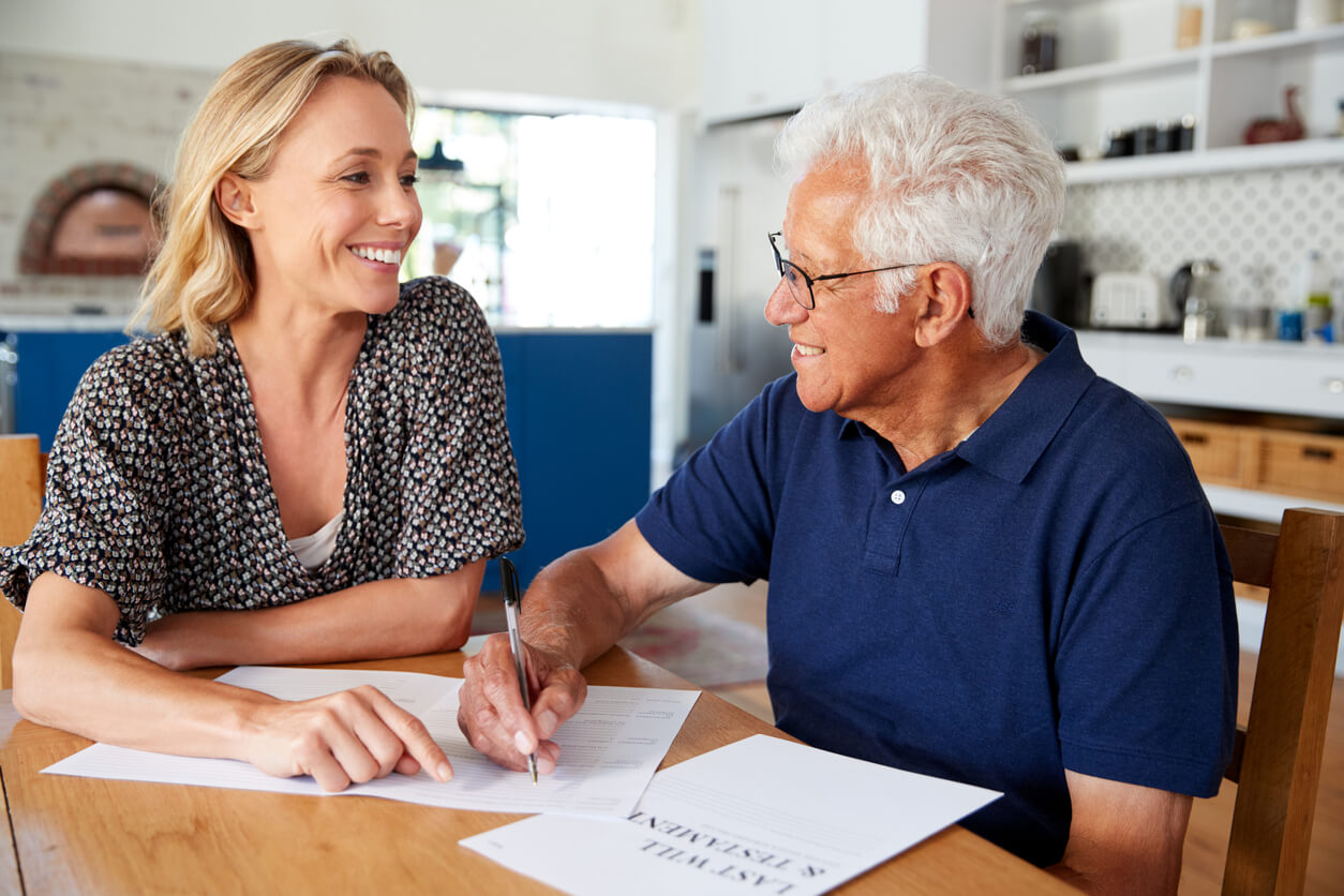 A woman helping an older man with his will