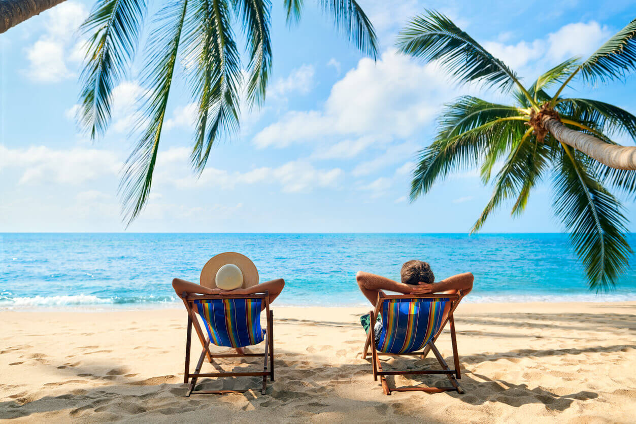 Two people relaxing in deck chairs on the beach