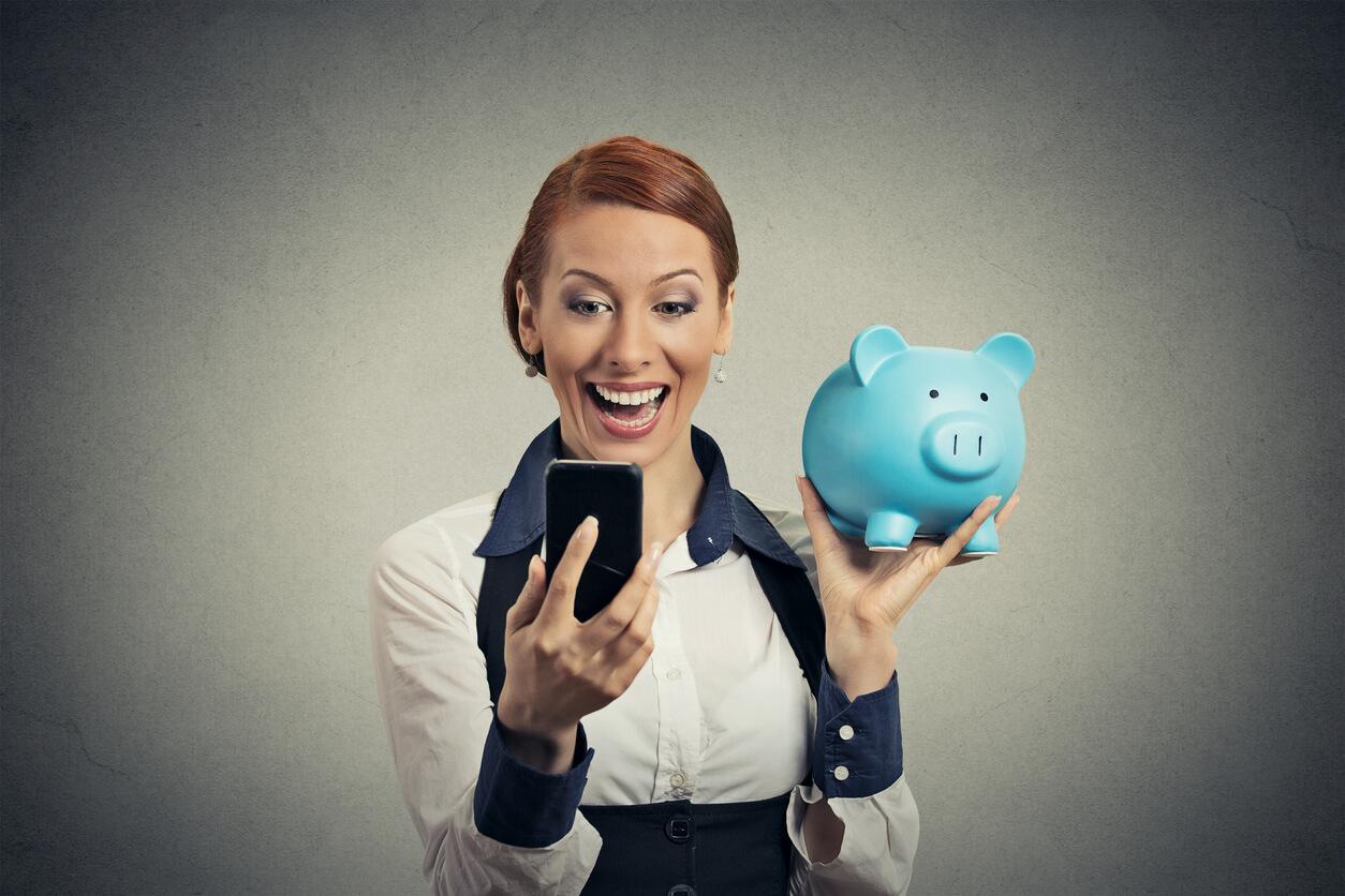 woman holding piggy bank using money saving app on phone