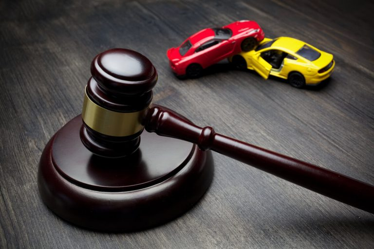 A gavel next to two toy cars showing an accident