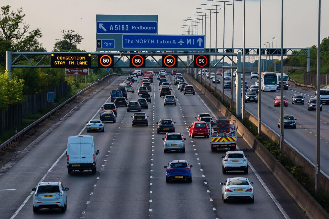 cars travelling on road under smart motorway gantry