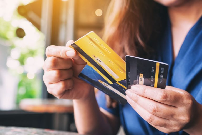 A woman holding three credit cards