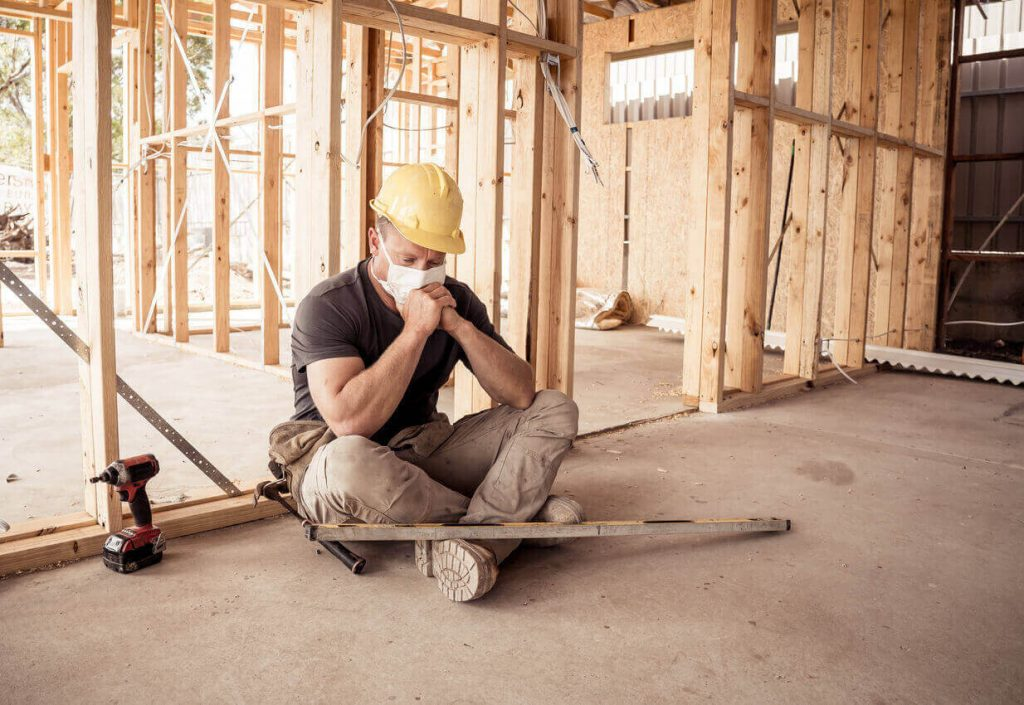 Self-employed construction worker sat on his own looking depressed